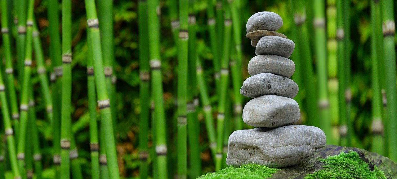 stacking rocks with bamboo background